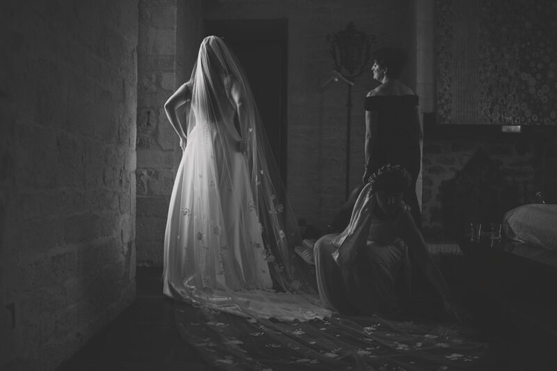 Bride standing in dark room lit by light through window - Picture by Rik Pennington Photography