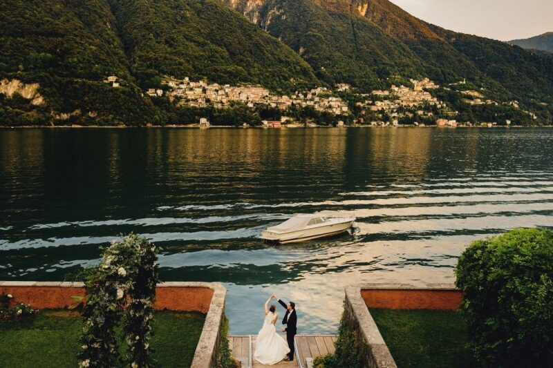Groom twirling bride by water in Italy - Picture by MIKI Studios