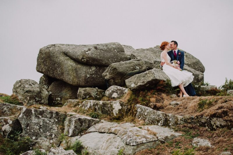 Bride and groom sitting on large rocks - Picture by Special Day Wedding Photos