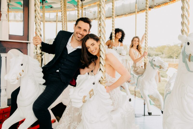 Bride and groom sitting on horses on fairground carousel - Picture by Emma-Jane Photography