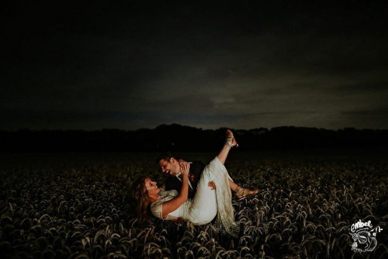 Groom carrying bride in wheat a field at night - Picture by Embee Photography
