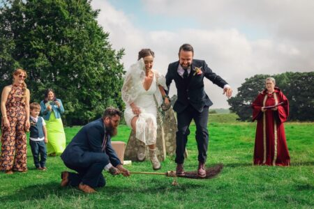 Bride and groom jumping over a broomstick during wedding ceremony - Picture by Twirly Girl Photography