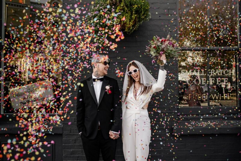 Bride and groom wearing sunglasses smiling as confetti falls around them - Picture by Epic Love Story