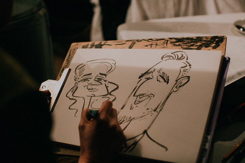 Caricaturist drawing guests at wedding