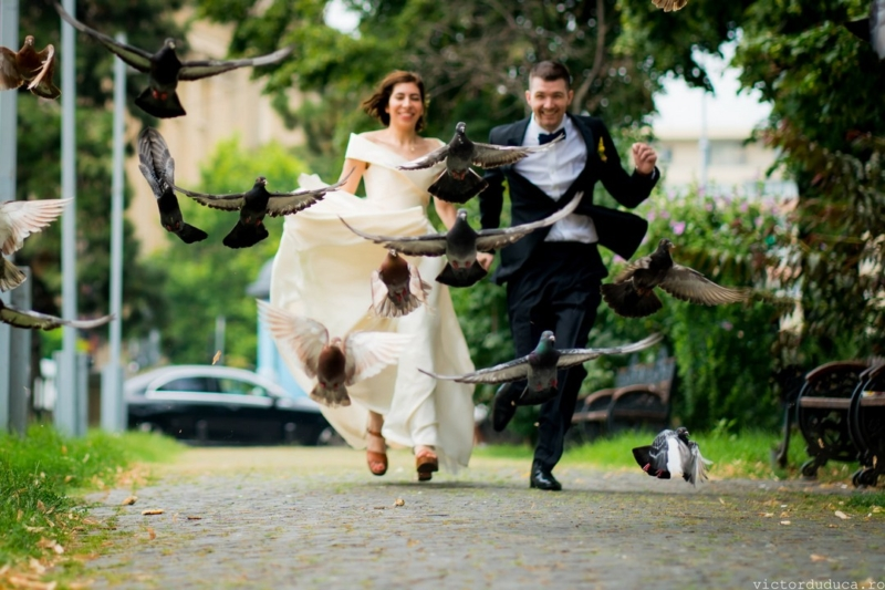 Lots of birds flying into the air as bride and groom run towards them - Picture by Victor Duduca