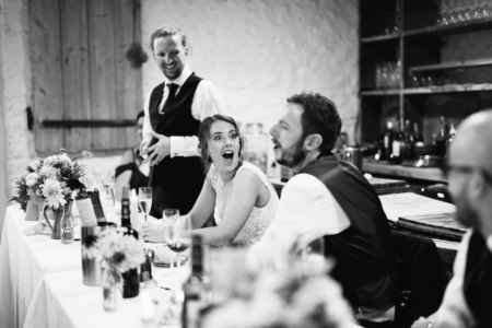 Bride looking at groom with shocked expression on her face during best man speech - Picture by Sam Gibson Photography